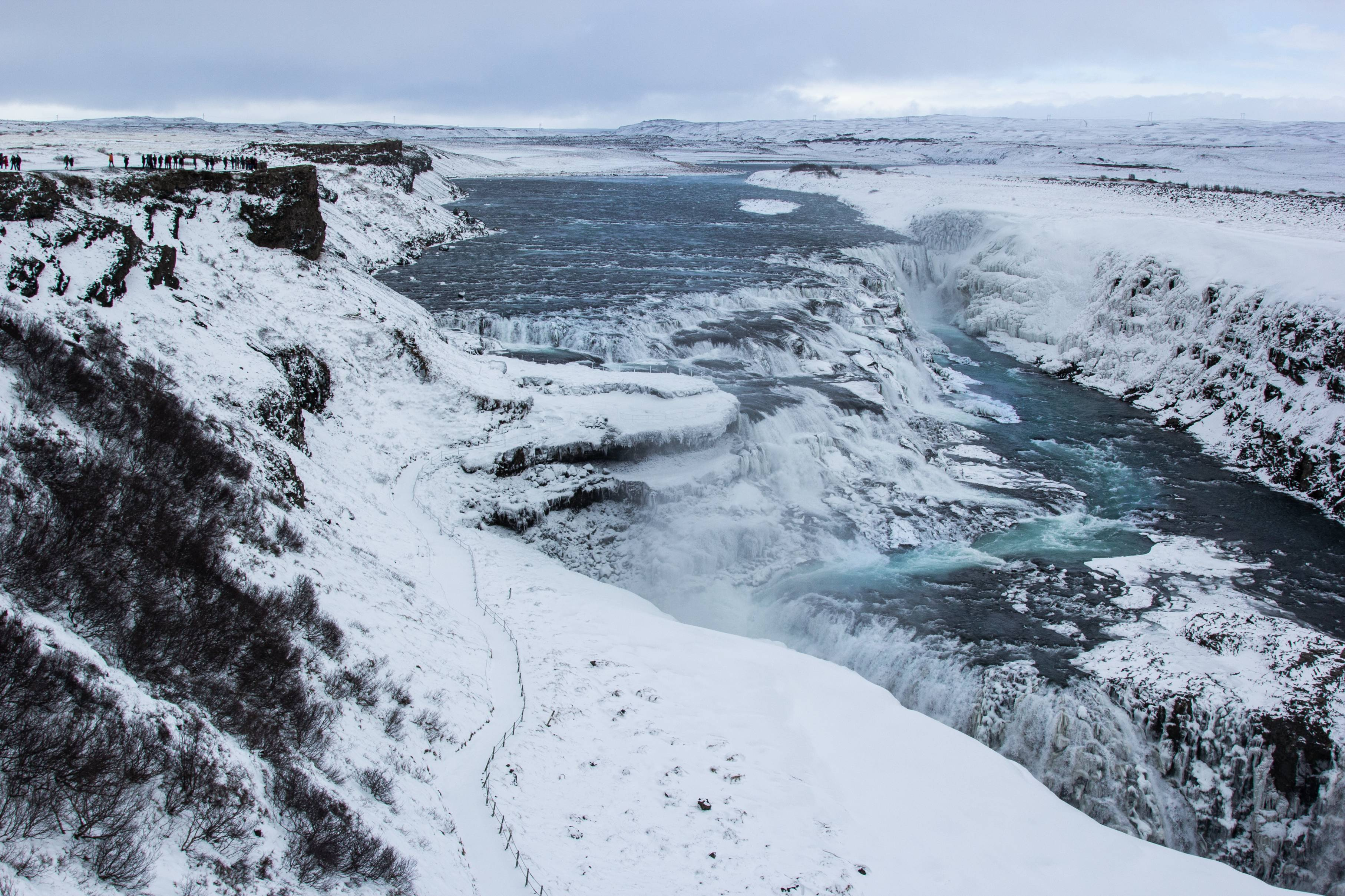 Gullfoss-waterfall-covered-in-snow-with-people-watching-from-a-cliff-side-above-on-the-left