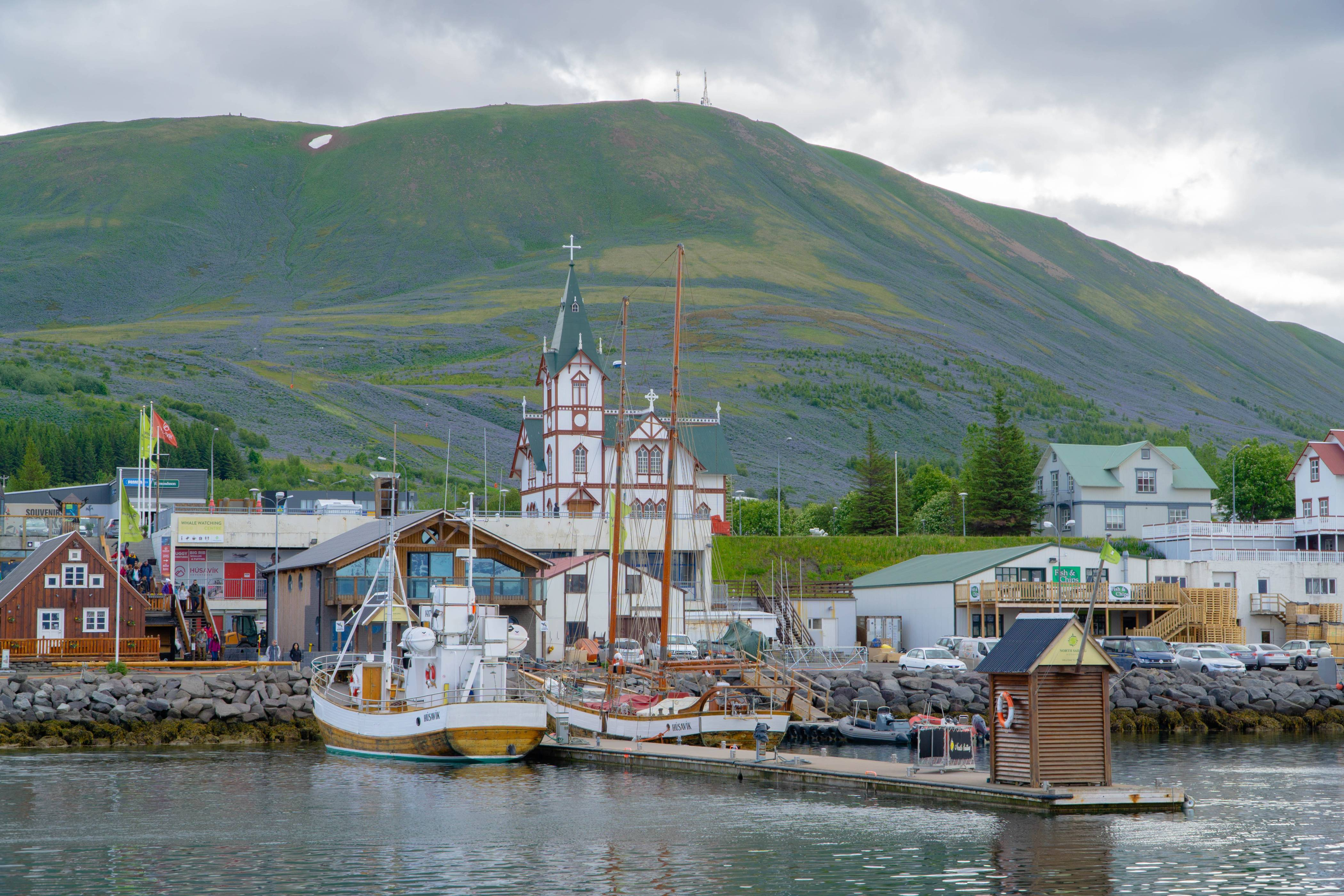 Husavik-harbor-with-two-small-boats-seen-from-the-ocean-with-husavik-church-in-the-background-on-a-summer-day