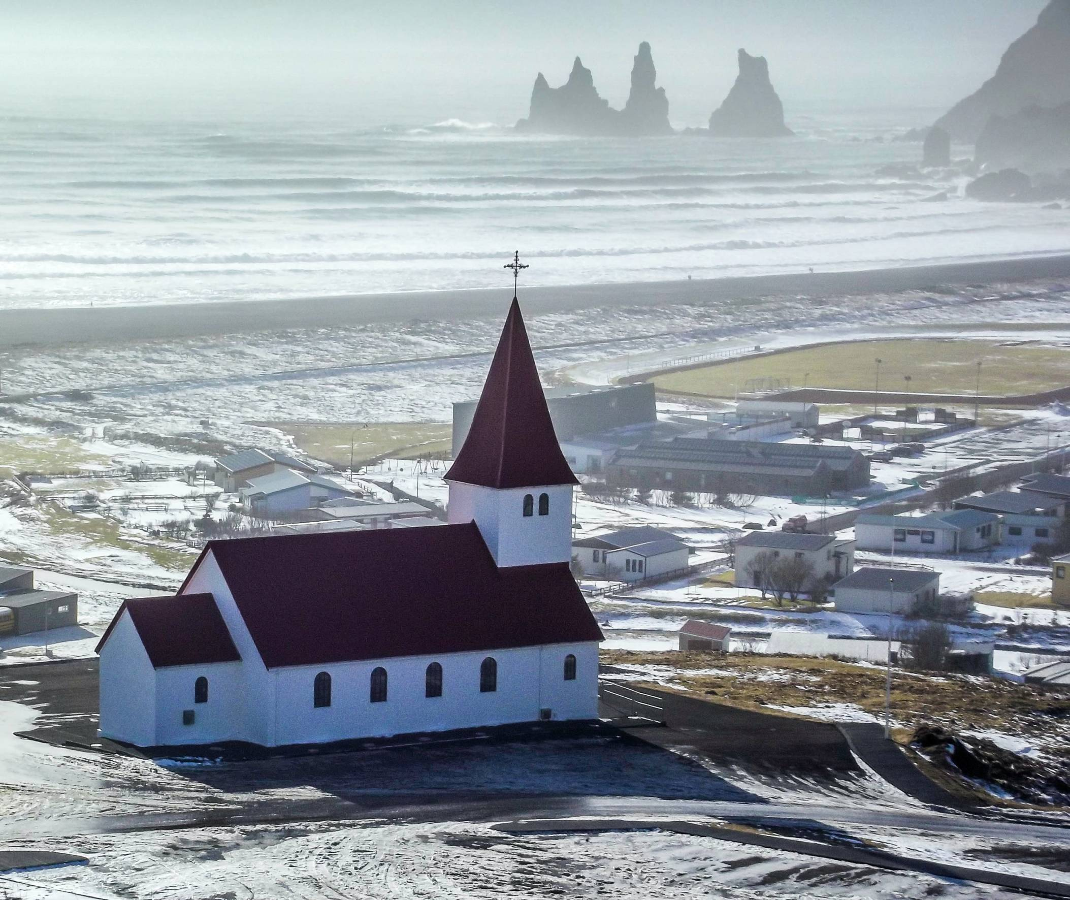 vik-church-with-town-and-reynisfjara-in-background-on-a-moody-rainy-day