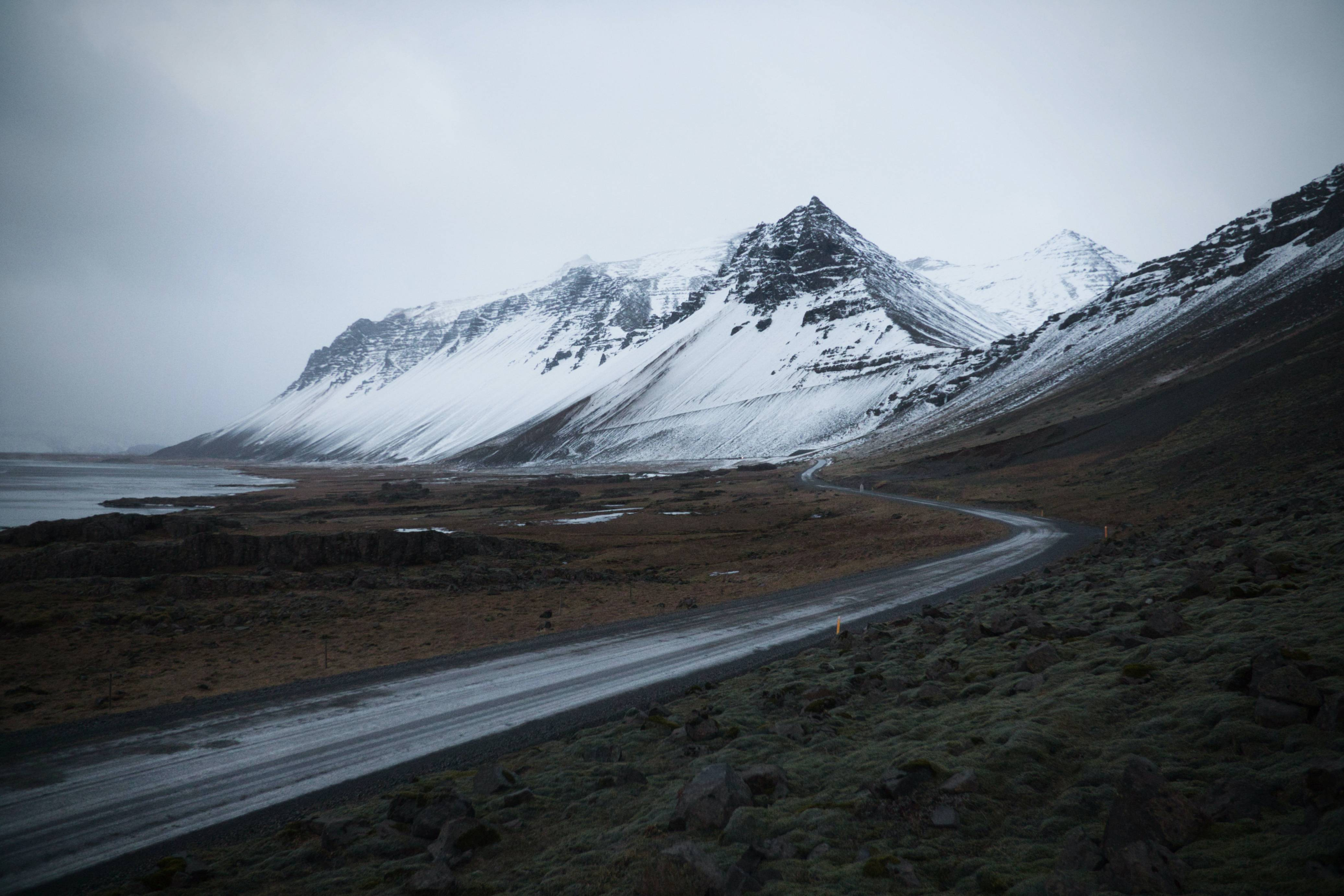 Icelandic-road-in-winter-along-the-coast-and-mountains-covered-in-snow-in-background
