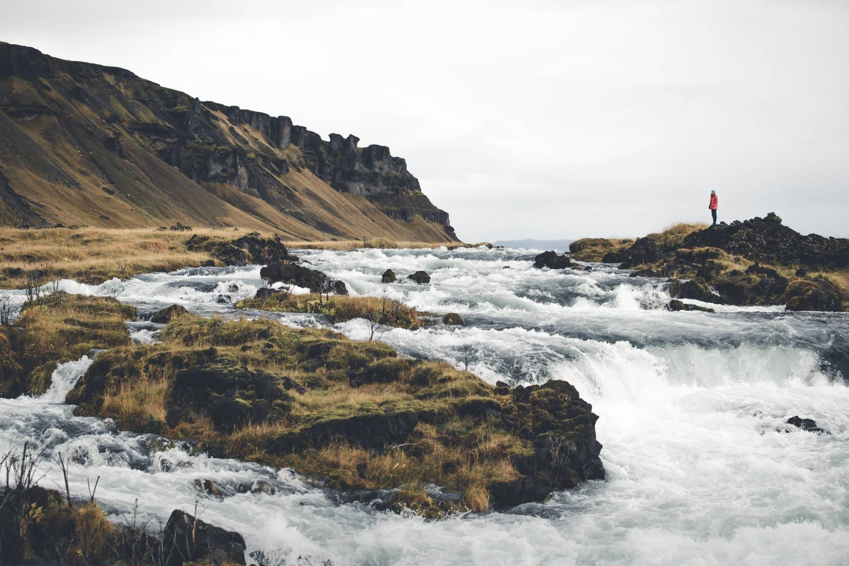 Woman-in-red-jacket-standing-by-river-in-Iceland-with-cliffs-on-a-cloudy-and-rainy-day