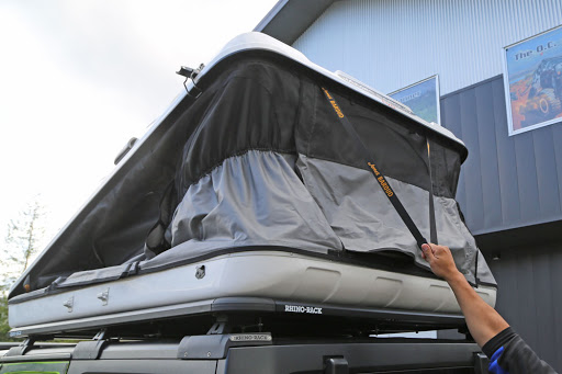 Man closing a roof top tent Iceland