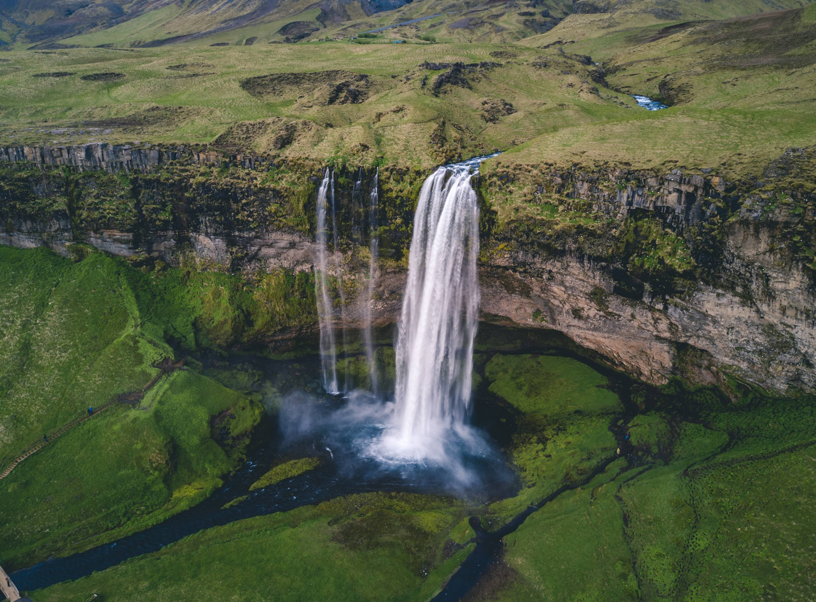 Seljalandsfoss-waterfall-seen-from-a-drone-above-on-a-summer-day-surrounded-by-green-grass